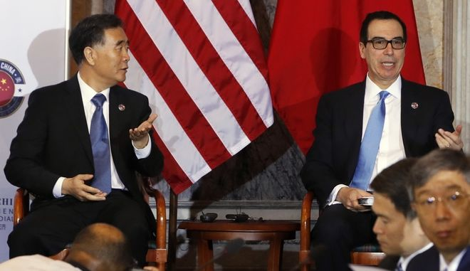 Chinese Vice Premier Wang Yang, left, and Treasury Secretary Steve Mnuchin, gesture that it's time to take their seats after speaking at the opening of the U.S.-China Comprehensive Economic Dialogue, Wednesday, July 19, 2017, at the Treasury Department in Washington. (AP Photo/Jacquelyn Martin)
