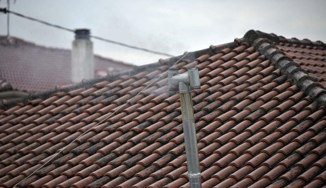 Καπνός βγαίνει από σωλήνα ξυλόσομπας σε σπίτι στην πόλη των Τρικάλων την Δευτέρα 23 Οκτωβρίου 2017. Ο καιρός παρουσίασε μεταβολή από νωρίς το πρωί της Δευτέρας στο νομό Τρικάλων, με ισχυρές βροχές και καταιγίδες και με την θερμοκρασία να φτάνει τους 18 βαθμούς Κελσίου το μεσημέρι. (EUROKINISSI/ΘΑΝΑΣΗΣ ΚΑΛΛΙΑΡΑΣ)