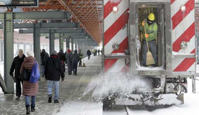 Commuters arrive and depart the Chicago's La Salle Street train station while METRA worker Kevin Doyle clear a doorway as a winter storm makes its way through several Midwest states Friday, Feb. 9, 2018, in Chicago.The upper Midwest is preparing for a wintry blast as a winter storm is expected across the region, with forecasters saying up to a foot of snow is expected in some areas. (AP Photo/Charles Rex Arbogast)