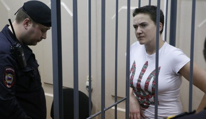 Ukrainian army pilot Nadezhda (Nadia) Savchenko looks out from a defendants' cage as she attends a court hearing in Moscow, November 11, 2014. Savchenko, who was earlier seized by separatists and then transported to Russia, is accused of involvement in the deaths of two Russian journalists killed during a military conflict in eastern regions of Ukraine, according to local media. REUTERS/Sergei Karpukhin (RUSSIA - Tags: CRIME LAW POLITICS MEDIA CONFLICT MILITARY) - RTR4DQN1