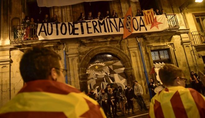 Pro independence supports wrapped by ''esteleda'' or Catalan pro independence flags stand in front a balcony while people protest with banner reading, ''Self determination'' in support of the Catalonia's secession referendum, in Pamplona, northern Spain, Sunday, Oct. 1, 2017.   Catalonia's defiant regional government is pressing ahead with a ballot on seceding from Spain.(AP Photo/Alvaro Barrientos)
