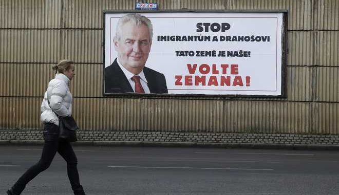 """In this picture taken on Wednesday Jan. 24, 2018, woman walks past a poster for presidential candidate Milos Zeman prior the second round of the presidential elections in Prague, Czech Republic.  The former head of the Academy of Sciences Jiri Drahos faces the pro-Russian incumbent Milos Zeman in a tight Czech presidential runoff vote Jan. 26-27, 2018. The poster reads """"Stop migrants and Drahos. This is our Land! Vote Zeman!"""" (AP Photo/Petr David Josek)"""
