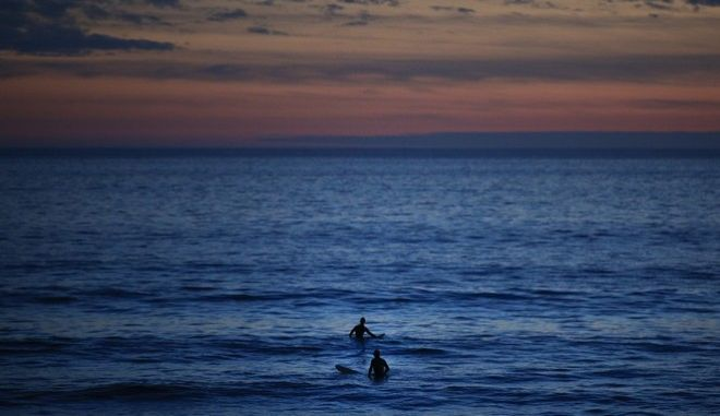 Two surfers wait for a wave in the Pacific Ocean at Sunset Beach in Pacific Palisades, Calif., Thursday, Jan. 4, 2018. (AP Photo/Jae C. Hong)