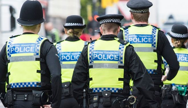 Five British Transport Police officers patrol the street in Highbury, London.