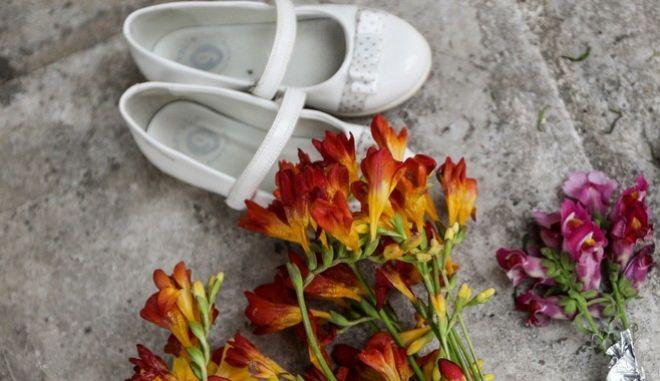 Παιδικά παπουτσάκια και λουλούδια έχουν αφήσει στο σημείο όπου εχθές το απόγευμα μητέρα και το παιδί της έπεσαν από τον 5ο όροφο πολυκατοικίας στον Νέο Κόσμο