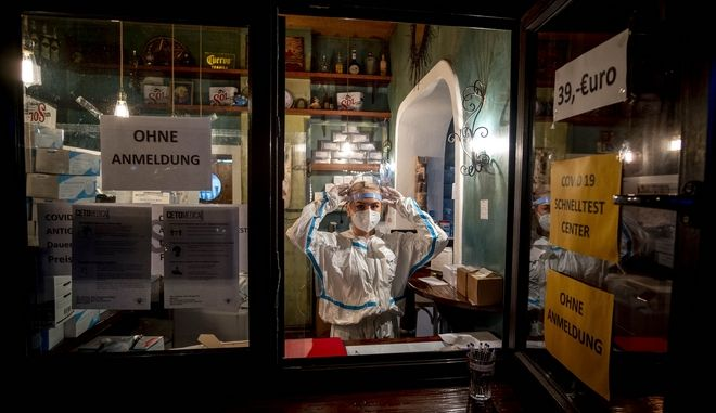 A medical worker waits for customers at a corona quick test center that is located in an empty tequila bar in Frankfurt, Germany, Tuesday, Dec. 15, 2020. Germany will go in a lockdown on Wednesday. (AP Photo/Michael Probst)