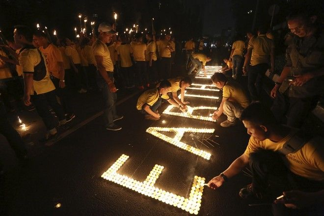 Πλήθος κόσμου κρατά αναμμένα κεριά σε διαδήλωση για το κλίμα, στην Ινδονησία