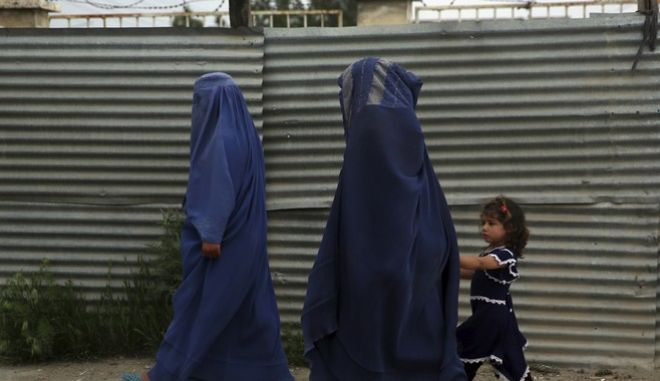 Women walk on the street during a quarantine in the holy fasting month of Ramadan in Kabul, Afghanistan, Tuesday, April 28, 2020. Muslims across the world are observing the holy fasting month of Ramadan, when the faithful refrain from eating, drinking and smoking from dawn to dusk. (AP Photo/Rahmat Gul)
