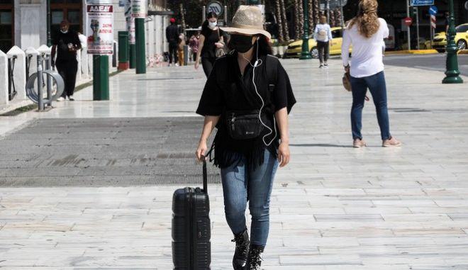 Γυναίκα περπατά στο κέντρο της Αθήνας