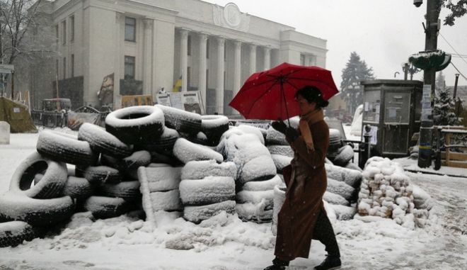 During heavy snow a woman passes by a tire barricade erected by supporters of the Movement of New Forces, the political party led by Mikheil Saakashvili in front of the parliament building in Kiev, Ukraine, Monday, Dec.18, 2017.   The streets around Parliament have been the scene of recent protests demanding hte resignation of Ukrainian President Petro Poroshenko. (AP Photo/Efrem Lukatsky)