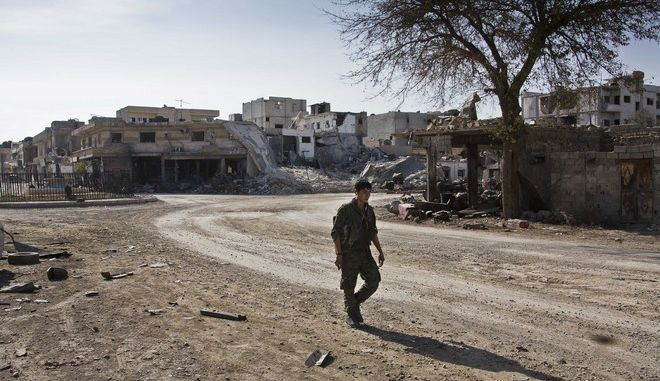 In this Wednesday, Nov. 19, 2014 photo, a Kurdish fighter walks past the town entrance circle heading to Kurdish strongholds in Kobani, Syria. Backed by small numbers of Iraqi peshmerga forces and Free Syrian Army rebels, Kurdish fighters, whose political founders espouse a firm left-wing ideology, are locked in fierce battles to push back militants of the Islamic State group, which swept into the town in mid-September.(AP Photo/Jake Simkin)