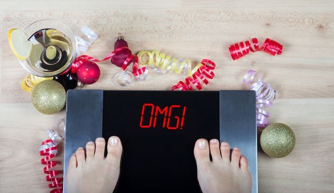 """Digital scales with female feet on them and sign""""omg!"""" surrounded by Christmas decorations and glass of vermouth. Shows how alcohol and unhealthy lifestile during xmas holidays effect our body."""
