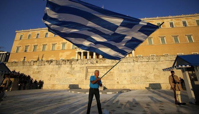 Άνδρας με την ελληνική σημαία έξω από τη Βουλή