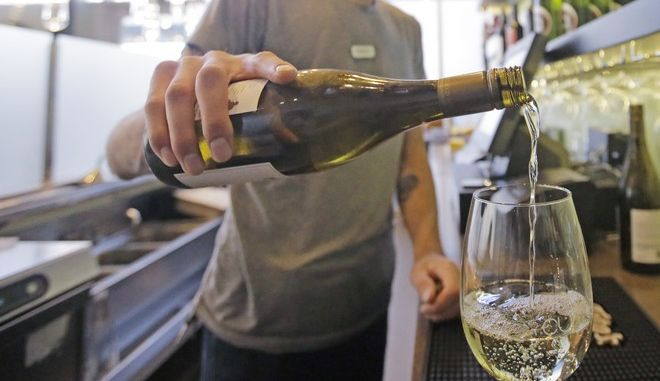 """This Wednesday, March 29, 2017, photo, Current Fish & Oyster Restaurant bartender Wren Kennedy pours wine behind the bar, in Salt Lake City. At Current Fish & Oyster Restaurant, a frosted glass wall covering a long, glossy bar will come down at the stroke of midnight on July 1, according to Joel LaSalle, one of the restaurant's owners. """"Not only is it ugly and covers up a beautiful bar, but it's costing us thousands of dollars in sales each month,"""" Some Utah restaurants are counting down the days until a new liquor law takes effect this summer, allowing eateries to take stop using walls and partitions that prevent customers from seeing their alcoholic drink being mixed and poured. (AP Photo/Rick Bowmer)"""