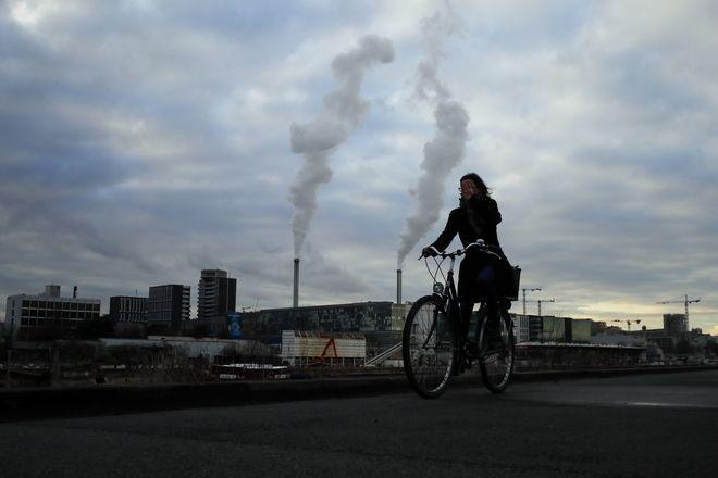 Ένα στιγμιότυπο αντίθεσης από τα προάστια του Παρισιού στις αρχές Δεκεμβρίου. Μια γυναίκα κάνει ποδήλατο την ώρα που τα φουγάρα της βαριάς βιομηχανίας ρυπαίνουν την ατμόσφαιρα.