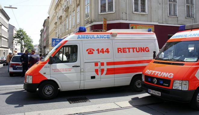 Ambulance and police cars stand next to a house in Vienna's Rudolfsheim district, housing an Indian temple, in which a shooting took place in Vienna, Austria, on Sunday, May 24, 2009. Police in Austria say up to 30 people have been wounded, nine severely, in a shooting at the Indian temple. Police spokesman Michael Takacs told Austria Press Agency five men entered a place of worship for an Indian religious community early afternoon Sunday and started firing at those present. Police arrested all five suspects, Takacs said. (AP Photo/Ronald Zak)