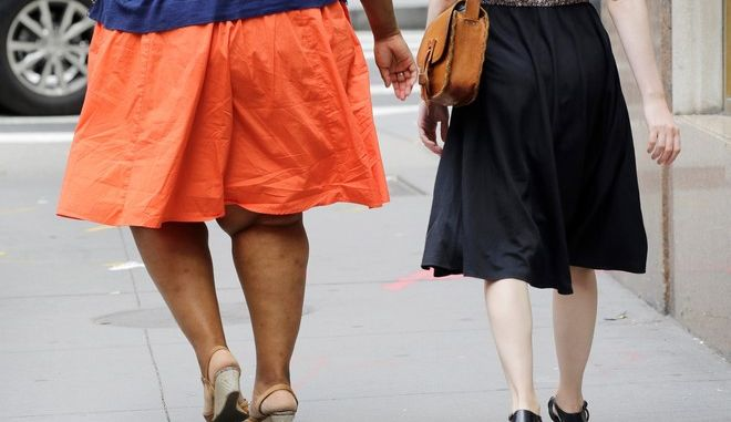 In this Monday, July 13, 2015 photo, an obese woman, left, walks in New York. One-third of American adults and one in six children are now obese, although an annual report released Thursday by two nonprofit groups found that rates could be stabilizing. The report noted that 25 states had obesity rates above 30 percent. In 2000, no state had a rate above 25 percent. (AP Photo/Mark Lennihan)