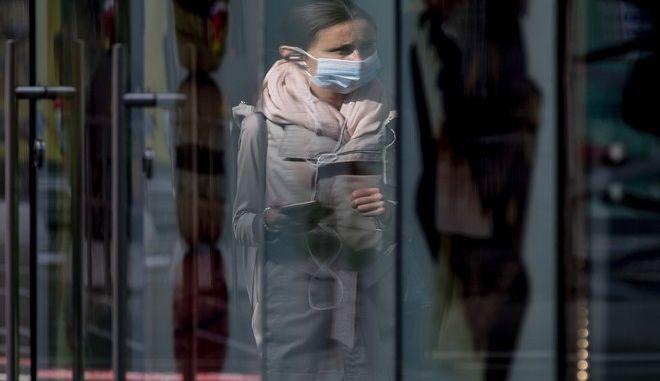 Γυναίκα με μάσκα μπροστά σε βιτρίνα.
