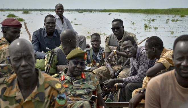In this photo taken Saturday, Aug. 19, 2017, South Sudanese army commander Col. James Gatjiath, center wearing beret, his son Charlie Chiong, 3rd right, and other government soldiers cross over to the west bank of the Nile in order to patrol the front lines, in the town of Kuek, northern Upper Nile state, South Sudan. Two years ago Chiong, the shy, lanky son of the commander was abducted by rebel forces amid the country's civil war and says he was held for a month in a roofless, mud-filled compound before escaping through a hole he dug between its bricks. (AP Photo/Sam Mednick)