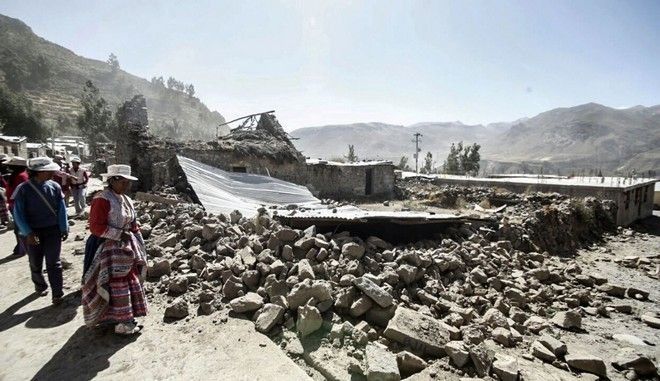 BEST QUALITY AVAILABLE - In this photo provide by the Peruvian government news agency ANDINA, a woman looks at the ruins of her home destroyed by an earhtquake in Chivay, Peru, Monday, Aug. 15, 2016. A shallow magnitude 5.4 earthquake centered in southern Peru's picturesque Colca Valley killed at least four people, including a 65-year-old U.S. tourist, and left some 30 injured as it toppled adobe homes. (ANDINA via AP)