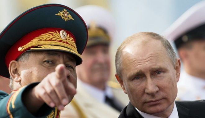 Russian President Vladimir Putin, right, listens to Defence Minister Sergei Shoigu during the military parade during the Navy Day celebration in St. Petersburg, Russia, on Sunday, July 30, 2017. (AP Photo/Alexander Zemlianichenko, Pool)