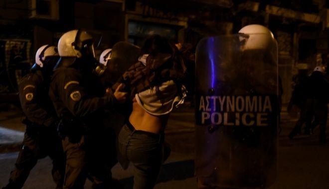 Αστυνομικοί σέρνουν νεαρή κοπέλα στα Εξάρχεια έχοντας τραβήξει την μπλούζα της.