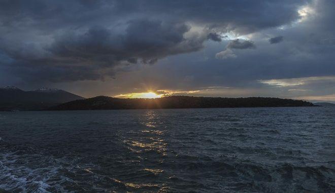Ο ήλιος δύει μέσα από τα σύννεφα του χειμωνιάτικου ουρανού και πίσω από το νησάκι του Αλατά που βρίσκεται απέναντι από την Μηλίνα στο νότιο Πήλιο.  (EUROKINISSI/ΘΑΝΑΣΗΣ ΚΑΛΛΙΑΡΑΣ)