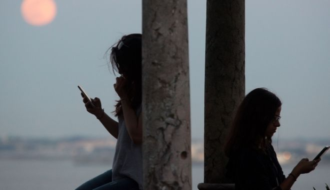 Two young women check their phone as a full Strawberry Moon, or Rose Moon, rises above the Tagus river in Lisbon Tuesday, June 2, 2015. Strawberry Moon was the name given by native American Algonquin tribes to the June full moon while in Europe it's often called Rose Moon. (AP Photo/Armando Franca)