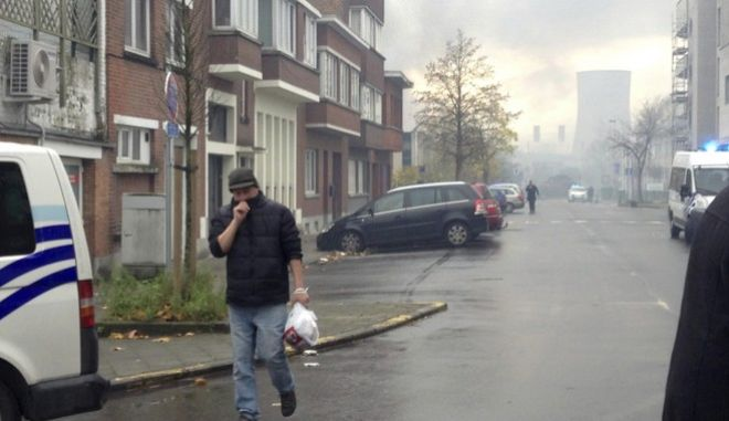 A man covers his face from smoke as he walks near the burning Milcamps waffle factory in Brussels, Thursday, Nov. 23, 2017. A fierce fire at a waffle factory cloaked part of Brussels in dense black clouds Thursday, disrupting road and rail traffic. The midday fire at the Milcamps factory producing the trademark Belgian waffles originated in the cooling system and quickly spread. There were no reports of injuries. (AP Photo/Mark Carlson)