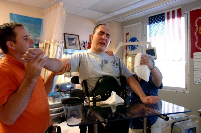 Physical Therapist David Isherwood, left,  takes Jose Pequeno through some exercises at the James A Haley Veteran's Hospital in Tampa, Fla. Nov. 2008.  Pequeno was critically injured in 2006 while serving with the New Hampshire National Guard in Iraq. He lost over half of his brain in an explosion and was in a coma for over four months.   (AP Photo/Tampa Tribune, Kathy Moore) ** ST. PETERSBURG, BRADENTON, LAKELAND, ALL MAGS OUT **