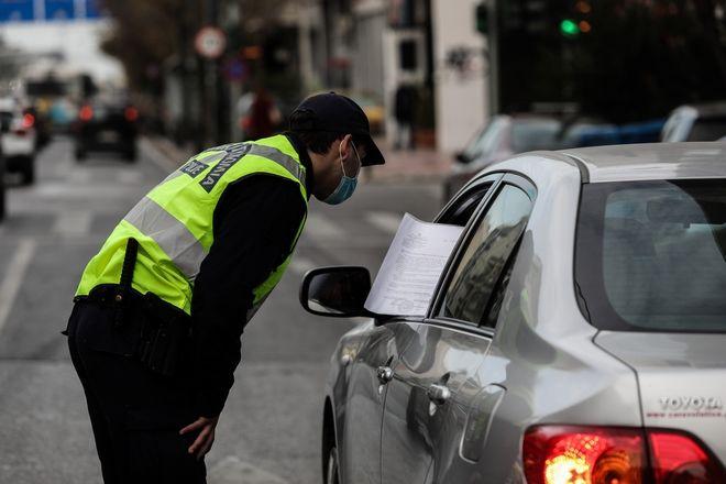 Αστυνομικός έλεγχει αυτοκίνητο σε δρόμο της Αθήνας.