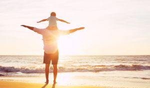 Πατέρας και γιος παίζουν στην παραλία με φόντο το ηλιοβασίλεμα