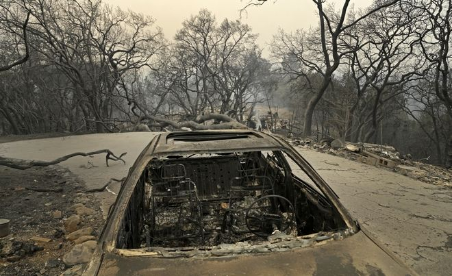 Remains of a car seen Monday, Oct. 9, 2017, on Crystal Road in Santa Rosa, Calif. Wildfires whipped by powerful winds swept through Northern California early Monday, sending residents on a headlong flight to safety through smoke and flames as homes burned. (AP Photo/Ben Margot)