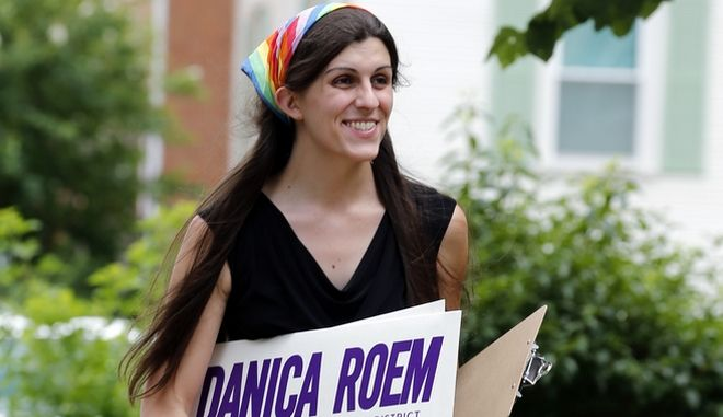 FILE - In this June 21, 2017, file photo, Democratic nominee for the House of Delegates 13th district seat Danica Roem brings campaign signs as she greets voters while canvasing a neighborhood in Manassas, Va. Roem, a former journalist, is challenging longtime incumbent Bob Marshall. If elected, Roem would be the states first transgender representative. (AP Photo/Steve Helber, File)