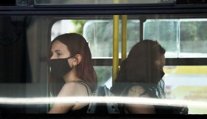 Γυναίκες με μάσκα σε λεωφορείο.