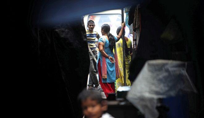 Ινδή ιερόδουλη μιλά σε νερό έξω από σπίτι της στα κόκκινα φανάρια της Kamathipura στο Μουμπάι