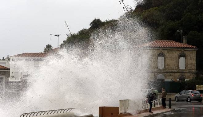 People stand as waves crash against the sea defenses in Marseille, southern France, Monday, Dec.11, 2017. Most of the French regions are on alert for violent storms, high winds and high coastal waves. (AP Photo/Claude Paris)