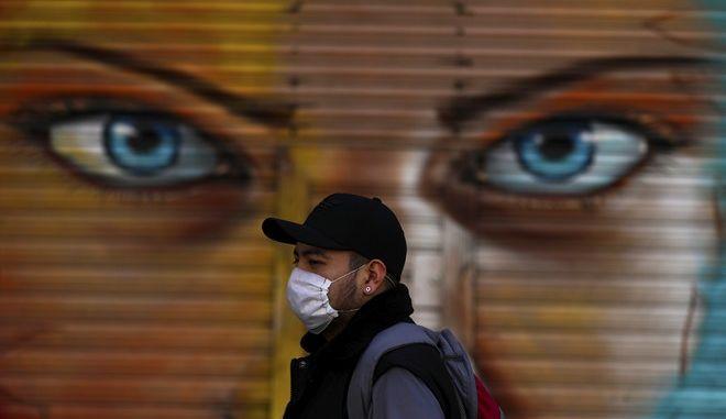 Πολίτης του Μεξικό περπατά με μάσκα μπροστά από γκράφιτι