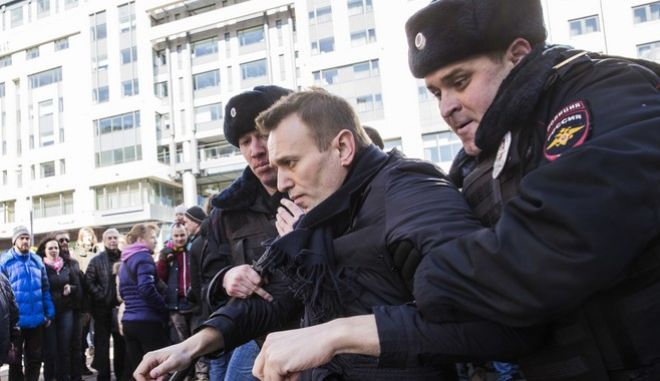 """In this photo provided by Evgeny Feldman, Alexei Navalny is detained by police in downtown Moscow, Russia, Sunday, March 26, 2017. Russia's leading opposition figure Alexei Navalny and his supporters aim to hold anti-corruption demonstrations throughout Russia. But authorities are denying permission and police have warned they won't be responsible for """"negative consequences"""" or unsanctioned gatherings. (Evgeny Feldman for Alexey Navalny's campaign photo via AP)"""