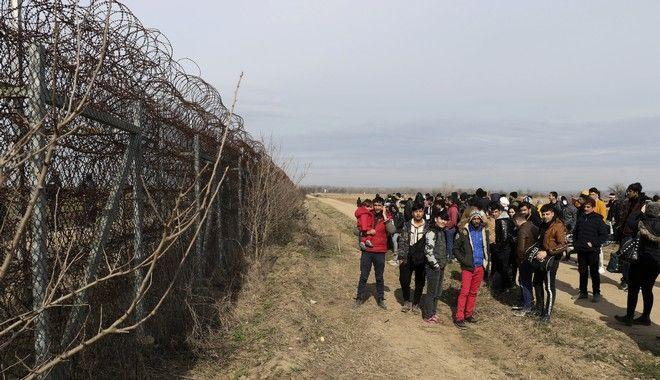 Πρόσφυγες στέκονται κοντά στον φράχτη στα ελληνοτουρκικά σύνορα