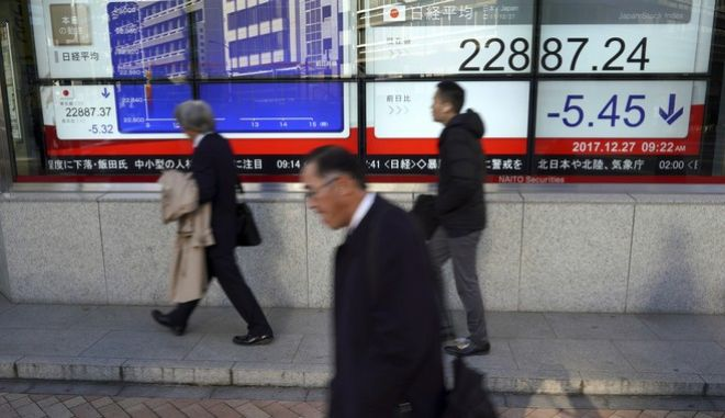 Men walk past an electronic stock board showing Japan's Nikkei 225 index at a securities firm in Tokyo Wednesday, Dec. 27, 2017.  Asian indexes were mixed Wednesday in quiet holiday trading after oil prices erased some of its recent gains and the region generally shrugged off the dip in technology stocks on Wall Street.(AP Photo/Eugene Hoshiko)