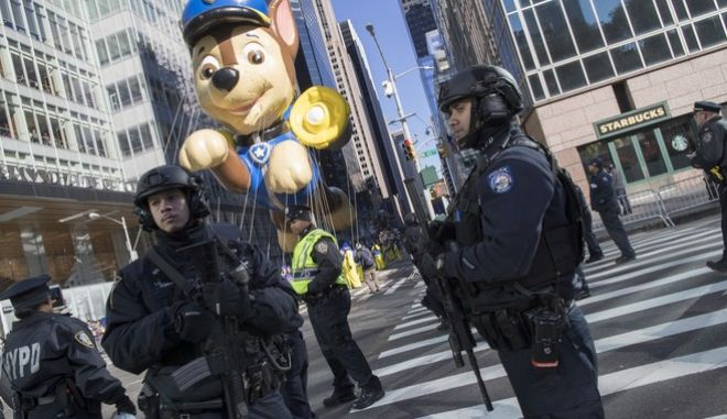 Heavily armed New York police officers stand guard on the parade route during the Thanksgiving Day parade in New York, Thursday, Nov. 23, 2017. (AP Photo/Mary Altaffer)