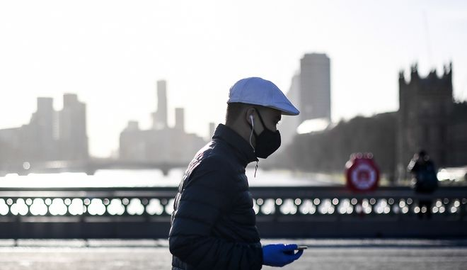 A man wears a face mask and disposable gloves as he walks on Westminster Bridge, in London, Tuesday, Dec. 15, 2020. London and its surrounding areas will be placed under Britain's highest level of coronavirus restrictions beginning Wednesday as infections rise rapidly in the capital, the health secretary said Monday, adding that a new variant of the virus may be to blame for the spread. (AP Photo/Alberto Pezzali)