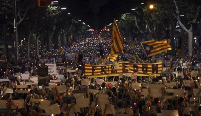 People gather to protest against the National Court's decision to imprison civil society leaders without bail, in Barcelona, Spain, Tuesday, Oct. 17, 2017. Protesters were gathering for a fresh round of demonstrations in Barcelona Tuesday to demand the release of two leaders of Catalonia's pro-independence movement who were jailed in a sedition probe. (AP Photo/Emilio Morenatti)