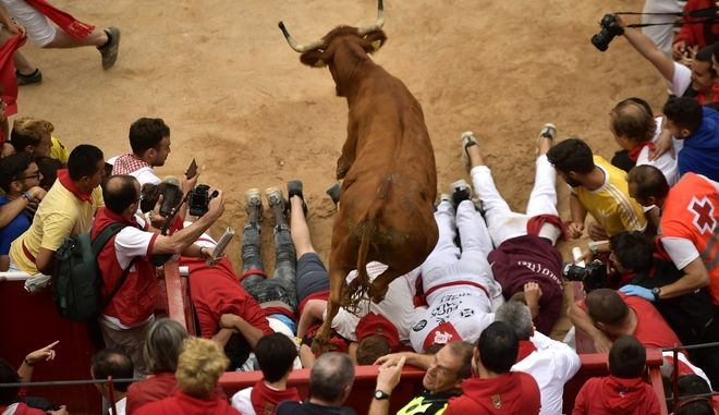 A cow jumps over men laid on the ground following the running of the bulls at the San Fermin Festival, in Pamplona, northern Spain, Friday, July 14, 2017. Revellers from around the world flock to Pamplona every year to take part in the eight days of the running of the bulls. (AP Photo/Alvaro Barrientos)