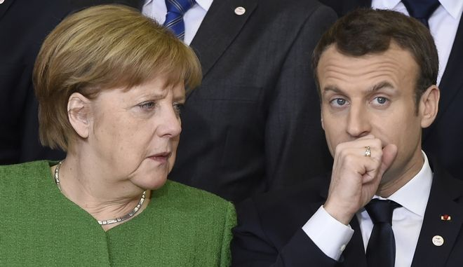 German Chancellor Angela Merkel, left, speaks with French President Emmanuel Macron during a group photo at an EU-Sahel meeting at EU headquarters in Brussels on Friday, Feb. 23, 2018. European Union leaders meet Friday with counterparts from Africa's Sahel in a show of support for the impoverished region fallen prey to extremists and a key transit point for migrants heading to Europe. (John Thys, Pool Photo via AP)