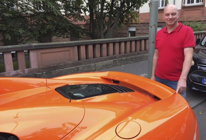 Markus Zahn stands at his sportscar in Giessen, Germany, Thursday, Sept. 28, 2017. The owner of the pricy McLaren sports car is in court to try to get a donkey owner to pony up for an alleged 5,000 euro (US$ 5,876) in damage caused when the animal chomped the backside of the vehicle. (Carolin Eckenfels/dpa via AP)