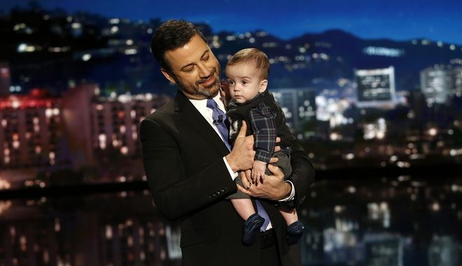 """This Dec. 11, 2017 image released by ABC shows host Jimmy Kimmel with his son Billy on """"Jimmy Kimmel Live!"""" Kimmel held his baby son as he returned to his late-night show after a week off for the boy's heart surgery. Kimmel kept up his ardent advocacy Monday night, urging Congress to restore the Children's Health Insurance Program, which has been left unfunded and stuck in a political stalemate since September. (Randy Holmes/ABC via AP)"""