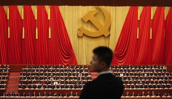 "A soldier in an usher uniform stands watch as Chinese President Xi Jinping, bottom, delivers a speech at the opening ceremony of the 19th Party Congress at the Great Hall of the People in Beijing, Wednesday, Oct. 18, 2017. Xi on Wednesday urged a reinvigorated Communist Party to take on a more forceful role in society and economic development to better address ""grim"" challenges facing the country as he opened a twice-a-decade national congress. (AP Photo/Andy Wong)"