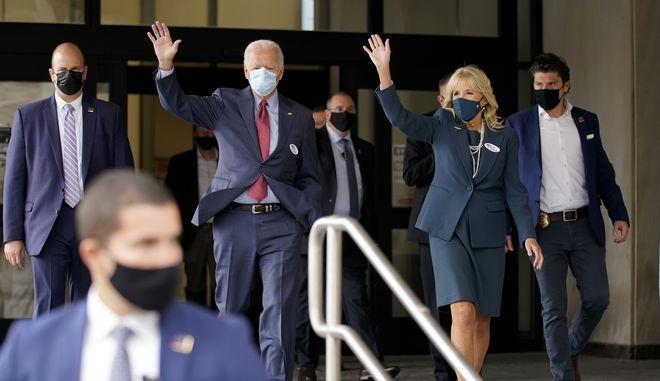 Ο Τζο Μπάιντεν και η σύζυγός του Τζιλ χαιρετούν τους δημιοσογράφους αφότου ψήφισαν σε εκλογικό κέντρο του Ντέλαγουερ